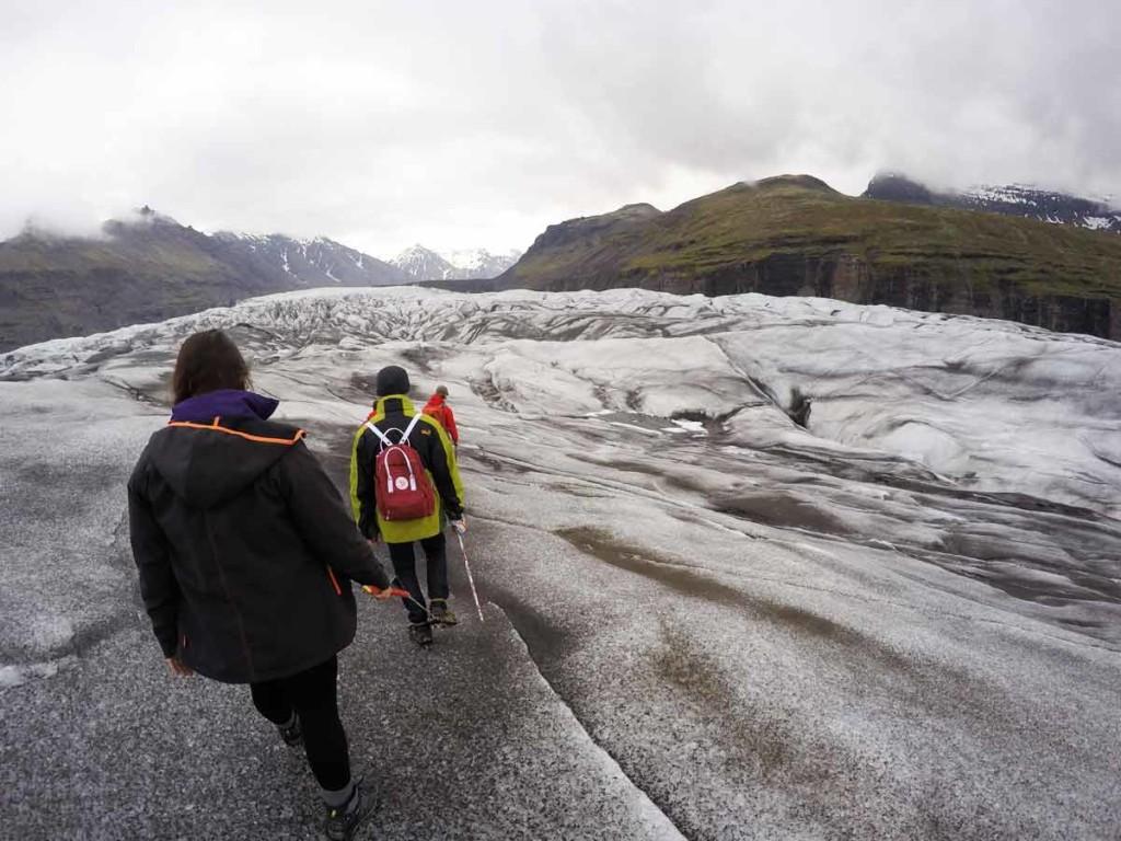 glacier walk pelo Vatnajökull. Na foto, duas pessoas aparecem fazendo a trilha sobre o gelo