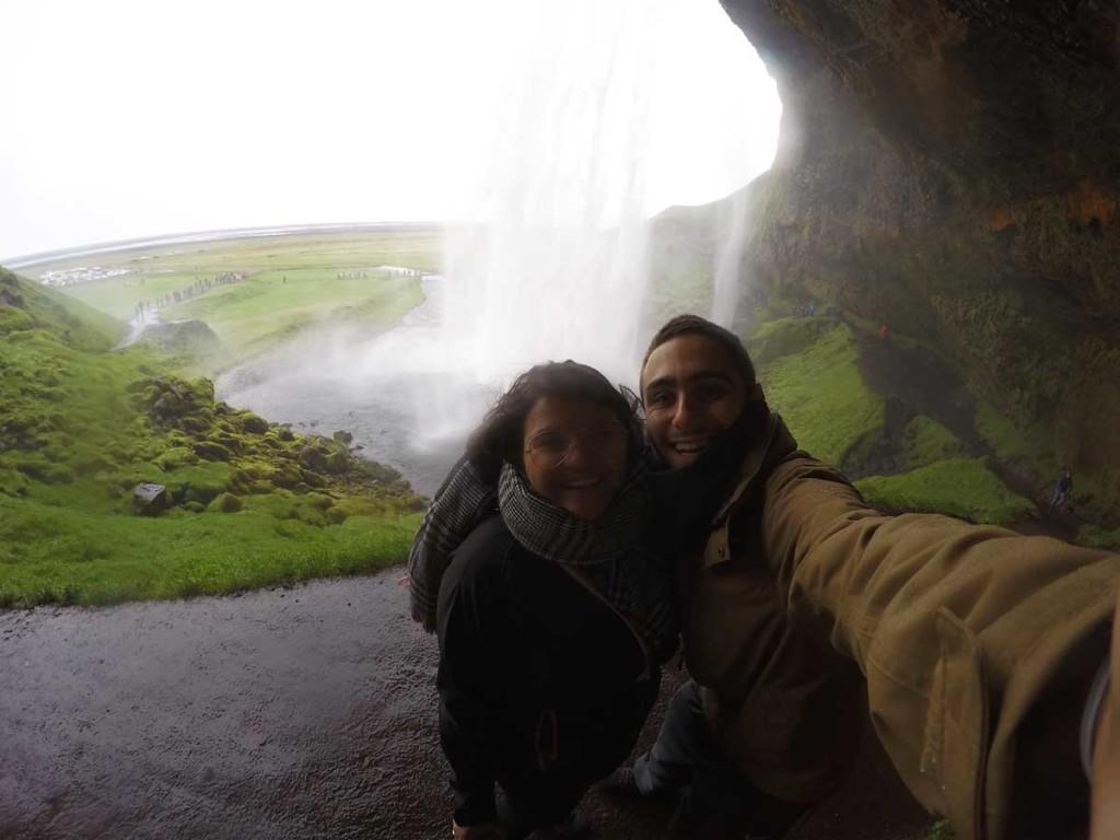cachoeira de Seljalandsfoss, na Islândia. Em primeiro plano aparecem duas pessoas, com a cachoeira ao fundo