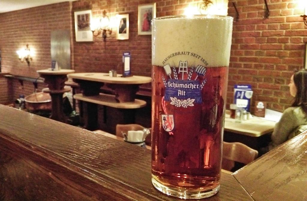 safari de cerveja dusseldorf cerveja alt em primeiro plano com o bar em segundo plano