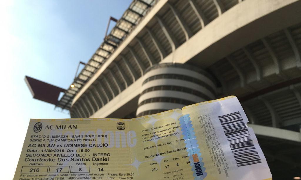 ingresso amarelo para entrar no estádio do Milan, o San Siro. Ao fundo da imagem está o próprio estádio