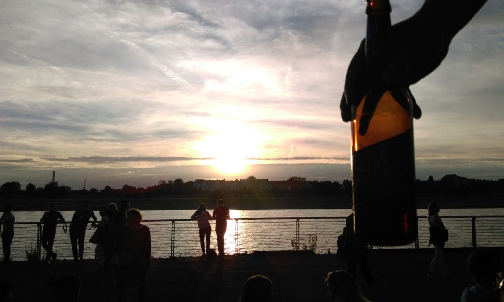 vista do rio reno a partir de uma escadaria em Dusseldorf, alemanha. COntra o sol está uma mão segurando uma cerveja