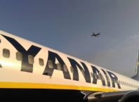 foto mostra aviao da ryanair em primeiro plano e um outro avião no ar em segundo plano