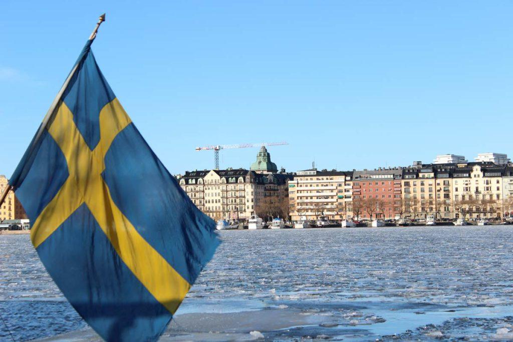 Foto baía de estocolmo com a bandeira sueca em primeiro plano e a cidade em segundo plano