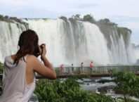 foto mostra turista tirando fotos de frente para as cataratas do iguacu em foz do iguacu no parana