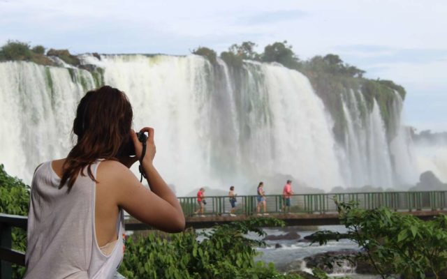 foto mostra turista tirando fotos de frente para as cataratas do iguacu em foz do iguacu no parana