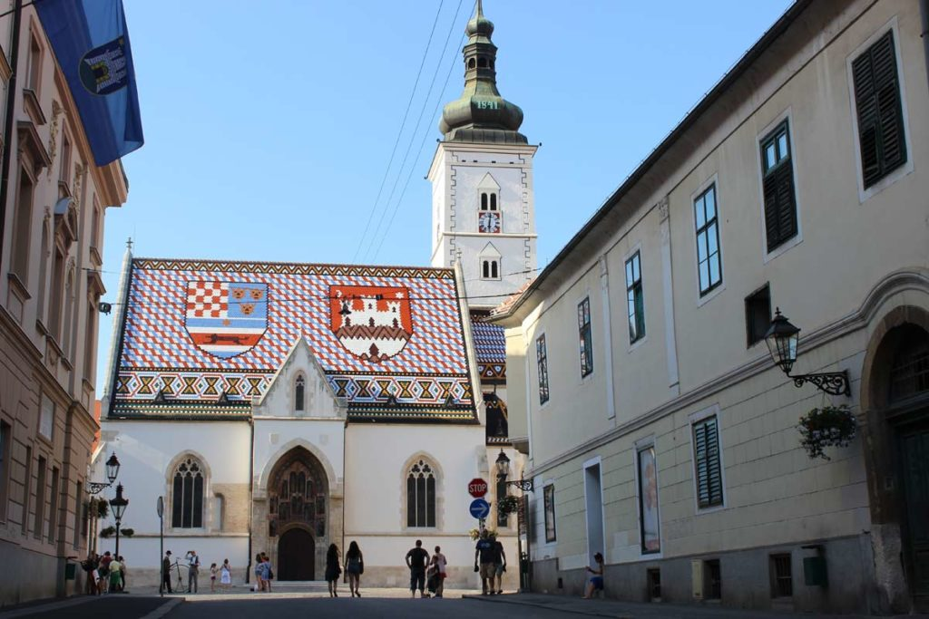 centro de zagreb na croácia - igreja possui um telhado vermelho com as cores e bandeirascroatas