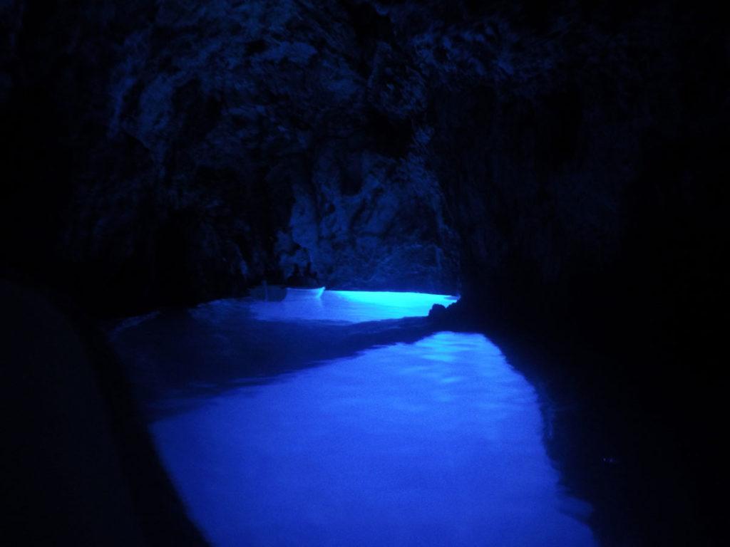 Dentro da blue cave, a cova azul em uma ilha croata. à frente está um pequeno barco e ao redor uma luz forte azul compõe o resto do cenário