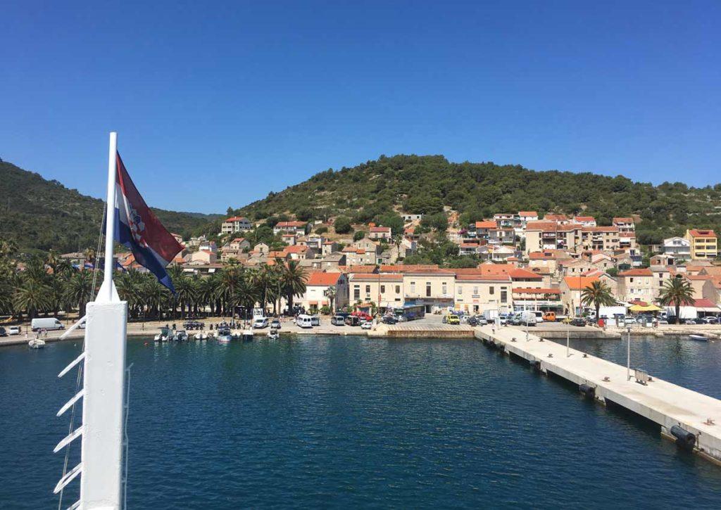 Ferry boat atracando em Vis. Bandeira da Croácia em primeiro plano e o centro da ilha em segundo plano, com prédios bege e montanha ao fundo