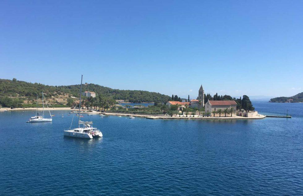 chegada na ilha de Vis de ferry boat. A frente, o mar com uma lancha ao centro e uma igreja na costa