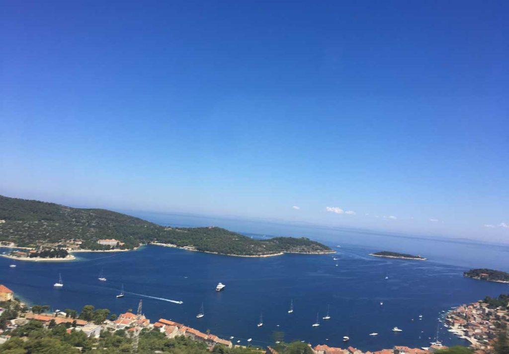 Vista aérea da ilha de vis, com a baía à frente rodeada por montanhas
