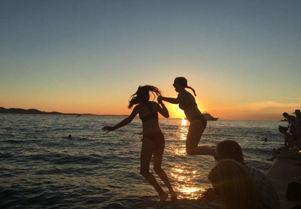 meninas pulam no mar de Zadar ao pôr do sol