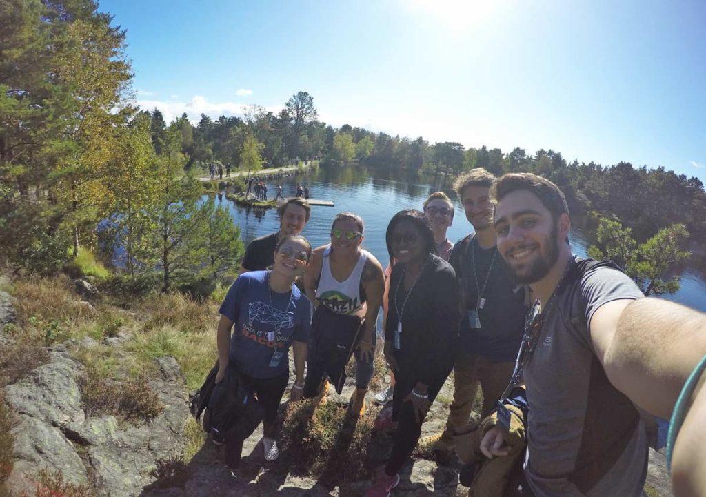 grupo reunido em parque na noruega com lago ao fundo