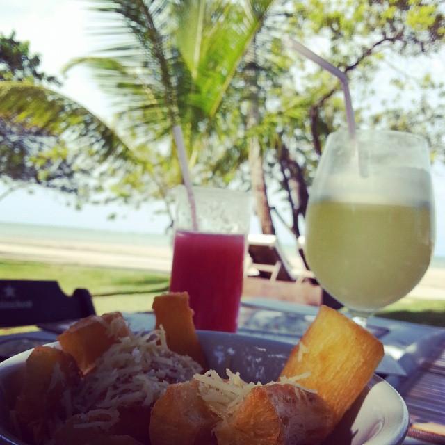 mandioca frita e suco de limao com coqueiros e praia ao fundo