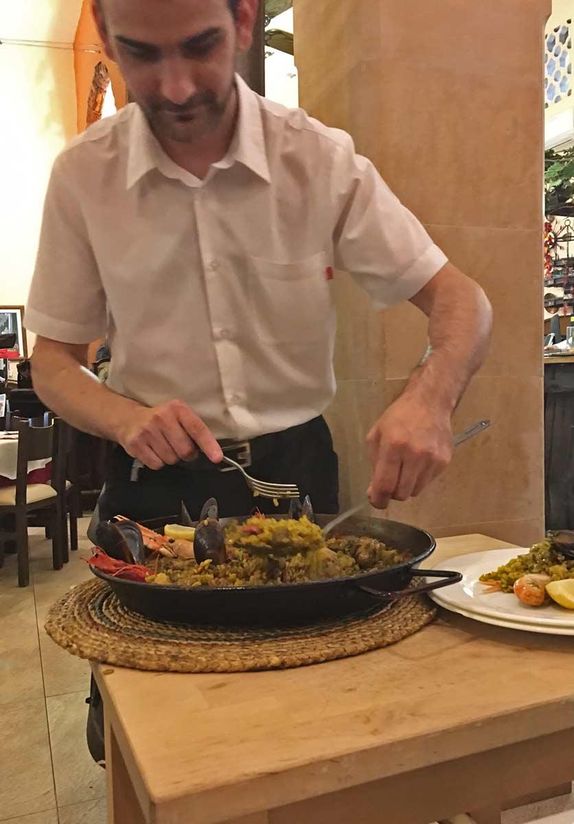garcom servindo paella em mesa de restaurante em pollenca