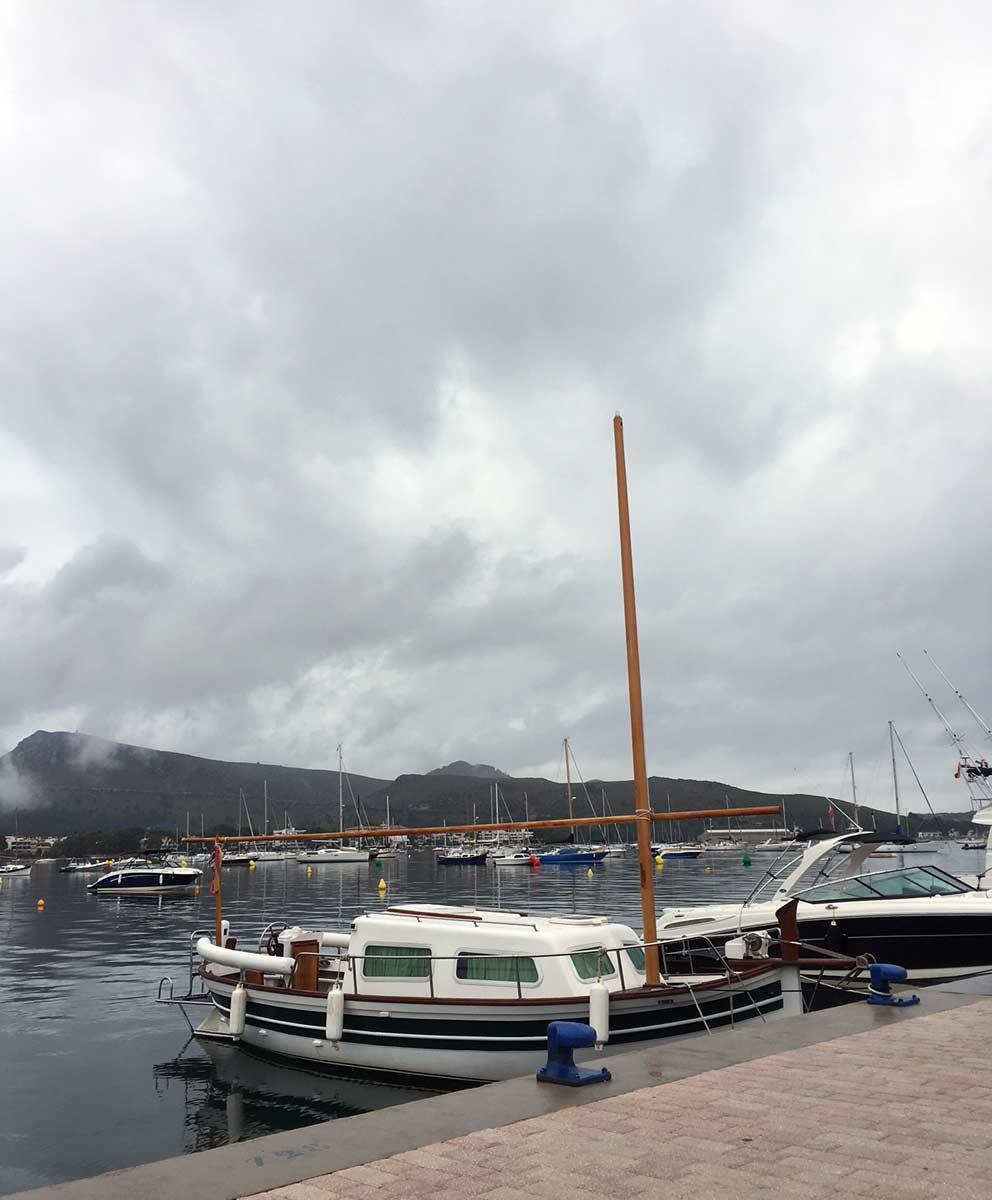 vista do port de pollenca, com barcos atracados e dia nublado