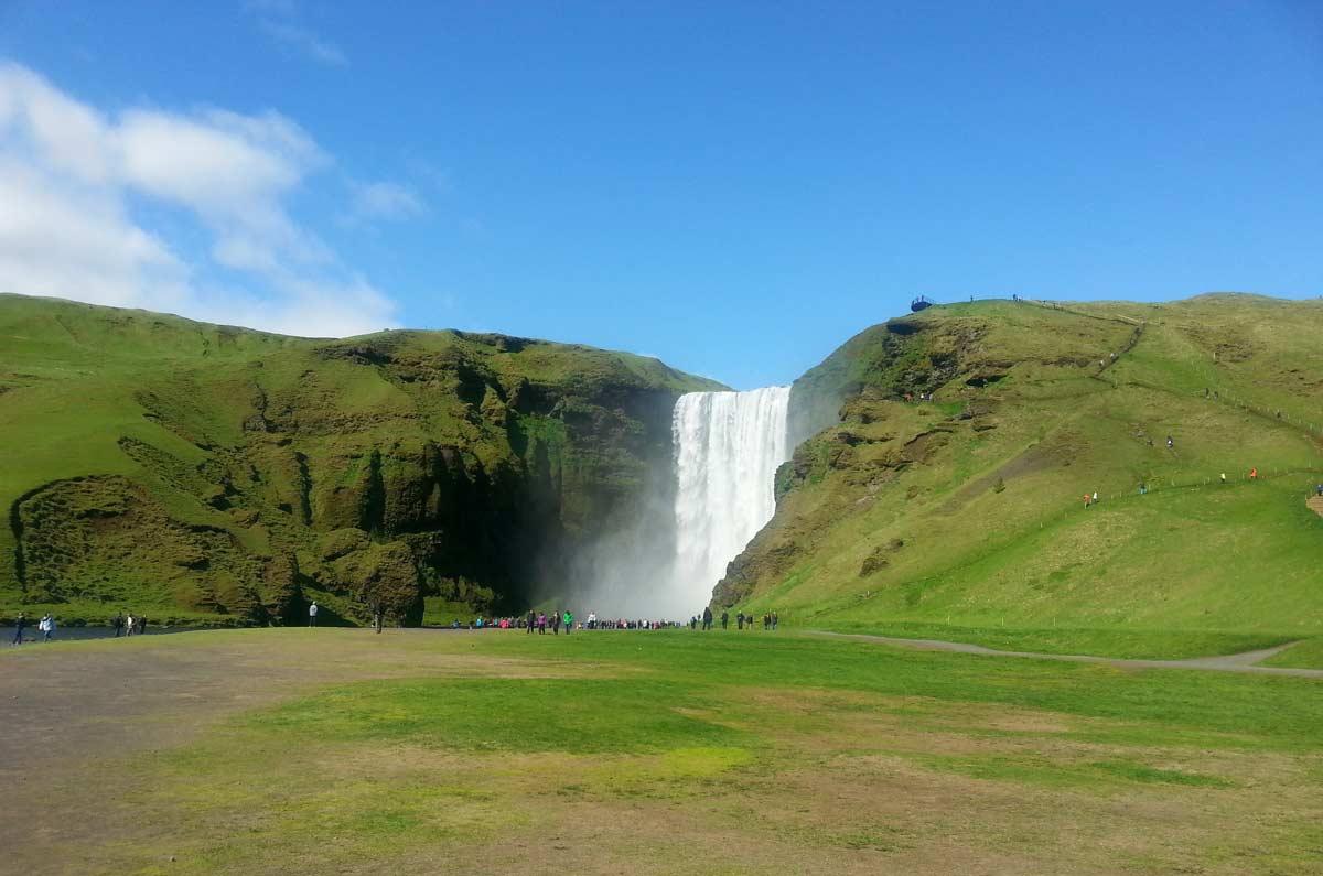 skogafoss, uma das cachoeiras mais bonitas da ilândia ao fundo da imagem, cercada de verde
