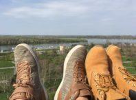 sapatos no primeiro plano com um rio em plano de fundo