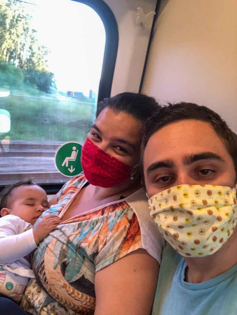 família viajando de trem de máscara